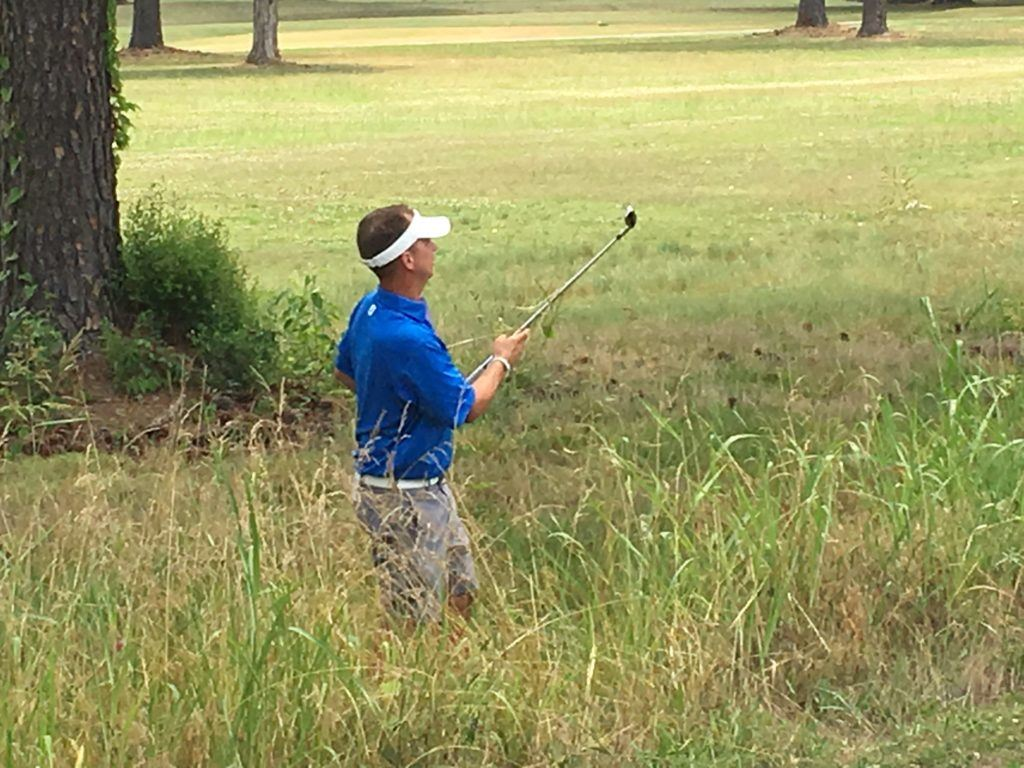 Jeremy McGatha follows the flight of his first shot out of the tall grass on 14 Saturday at Cane Creek. Despite finding hazards twice on the hole, McGatha made par.