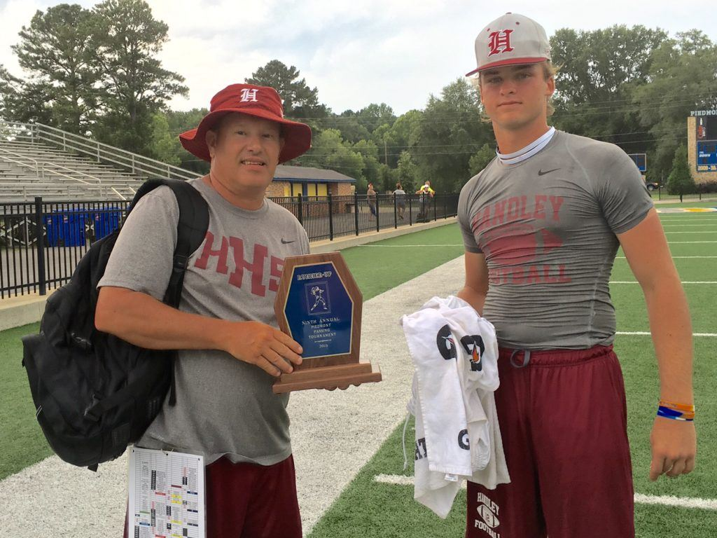Handley coach Larry Strain (L) and senior quarterback Rhett Fetner leave the field together after playing host Piedmont in the championship game of the Bulldogs' 7-on-7 tournament Saturday.