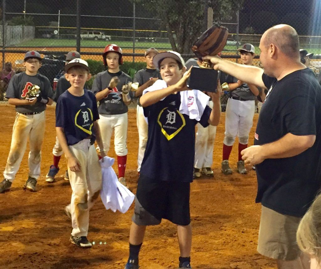 Honorary team member Caleb Watts, who recently lost his mother and grandmother in an auto accident, accepts the winner's trophy Sunday night after the East Alabama Dynasty won the BPA 12U World Series. (Special photo)