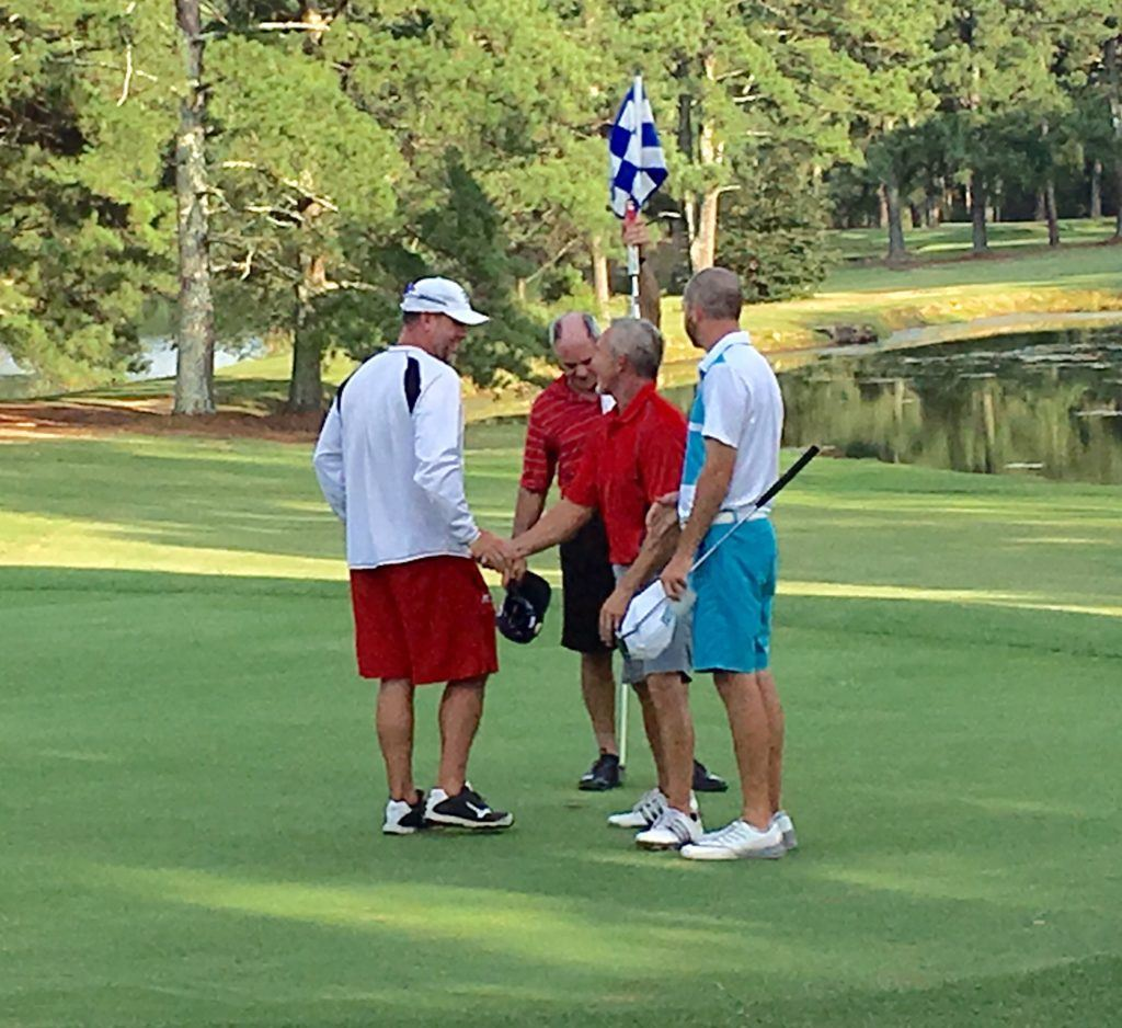 Ty Cole (L) is congratulated by his playing partners (from left) Chip Howell, Jeff Borrelli and Brennan Clay after winning the Pine Hill Invitational Sunday.