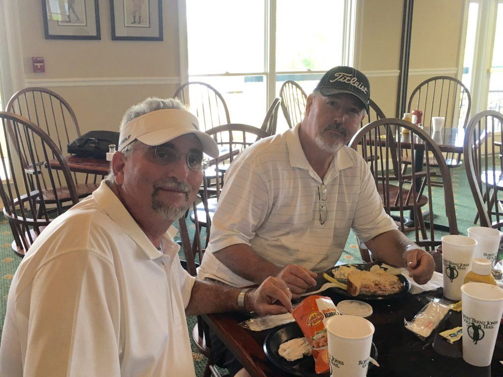 Bruce Collins (L) and Charles Estes enjoy a little lunch after being the first team to post 14-under-par 58 at Silver Lakes Friday.