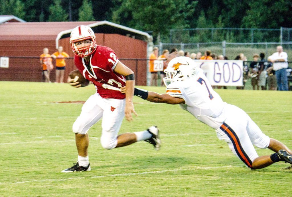 Wadley quarterback Connor Fordham (12) tries to escape the clutches of Woodland's Jordan Herring. (Photo by Christy Fordham)