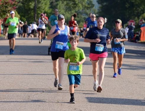 Nine-year-old Pierson Otralek of Anniston (196) races to stay ahead of Mendy Stephens (977) and Kanda Ford (657) at the finish of the Woodstock 5K.