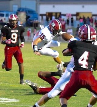 Sylacauga quarterback Jackson Walker (16) gets airborne against the Anniston defense as Tareeq Woods Packer (9) and Derrick McElderry (4) close ranks.