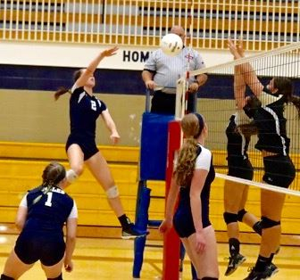 Jacksonville's Elizabeth Poe (2) plays the ball at the net in the first game of her team's match with Oxford Tuesday. On the cover, Oxford's Rachel Uhrin (30) gets it over. (Photos by B.J. Franklin/GungHo Photos)