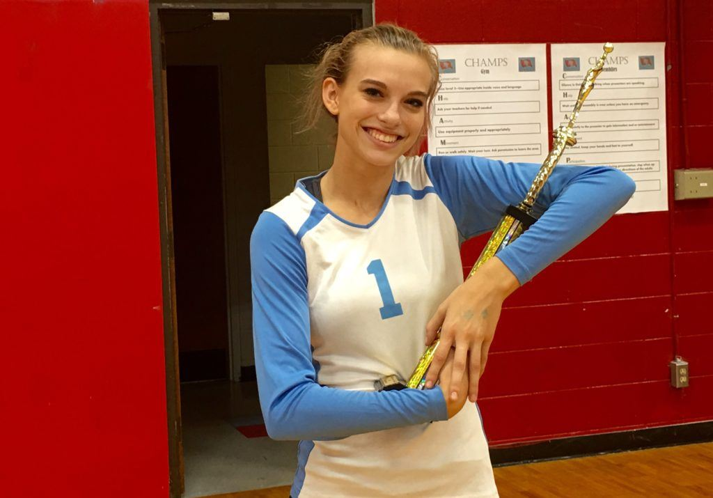 Cammy Cochran, one of two seniors on the undefeated Pleasant Valley volleyball team, cradles that trophy that went with winning Saturday's Sandy Hunter Invitational