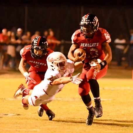 Weaver quarterback Dalton Hamby tries to run through the tackle of Ohatchee defender Jessie Sellers.