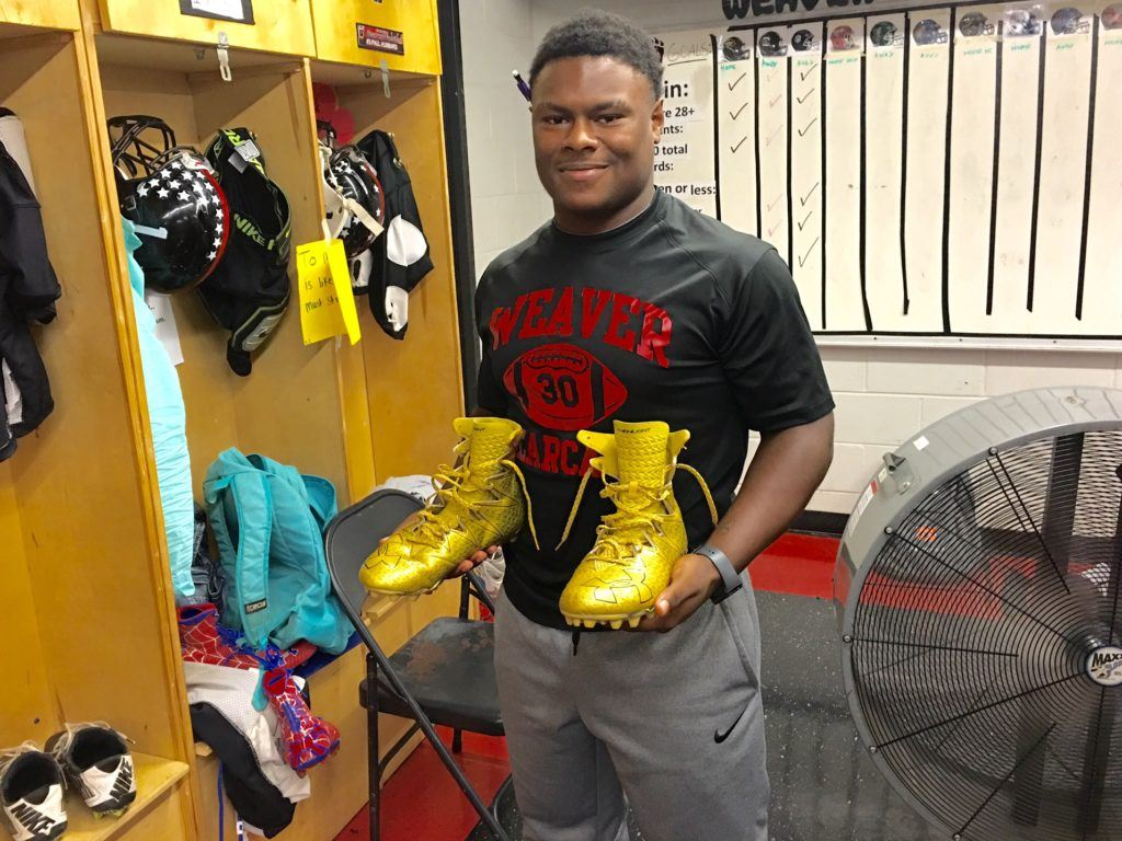 Weaver fullback Tyrik Hall shows off the gold cleats he's been playing in this season. Teammate Maurice Goodman's Spider-Man cleats can be seen in the lower left corner.