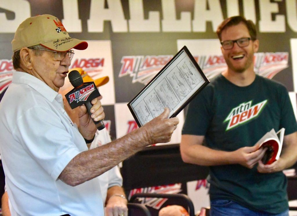 Dale Earnhardt Jr. (R) laughs as Donnie Allison displays a collage of Junior's paychecks when he worked in Allison's shop as a teenager. On the cover, Earnhardt is welcomed as an honorary member of the Alabama Gang by (from left) Donnie Allison, Red Farmer and Bobby Allison. (Photos by B.J. Franklin/GungHo Photos)