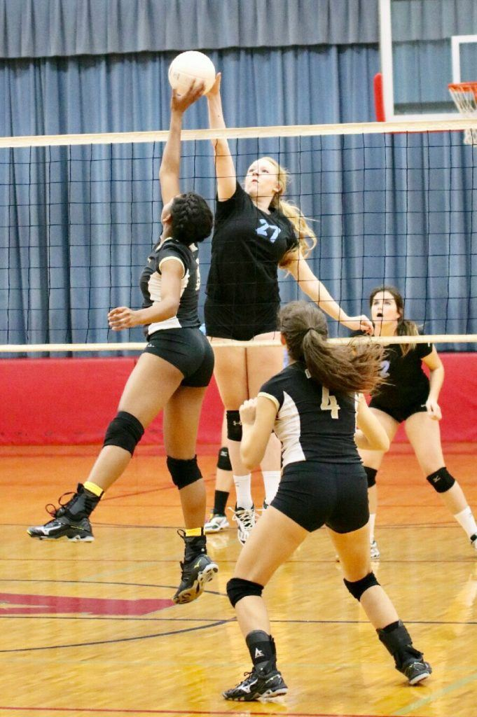 Pleasant Valley's Blakely Malsy (24) meets Oxford's Nyia Archie at the net for a block.