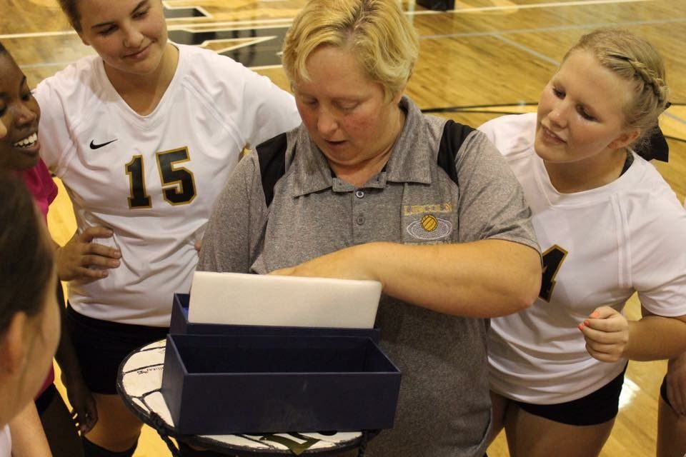 Lincoln volleyball coach Patty Hansen is surrounded by her players as she opens the box containing the crystal trophy commemorating her 500th career victory.
