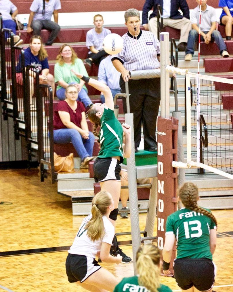Faith Christian's Nicole Frechette sends a shot back across the net against Sacred Heart.