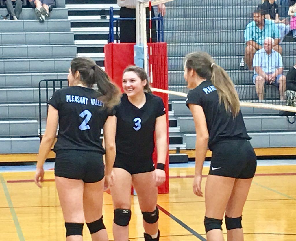 Pleasant Valley setter Anna Bryant (3) shares a laugh on the floor with teammates Alisa St. John (2) an Mikayla Kendrick during Friday's area tournament title match. On the cover, the PV players celebrate with a few pickle-cicles.