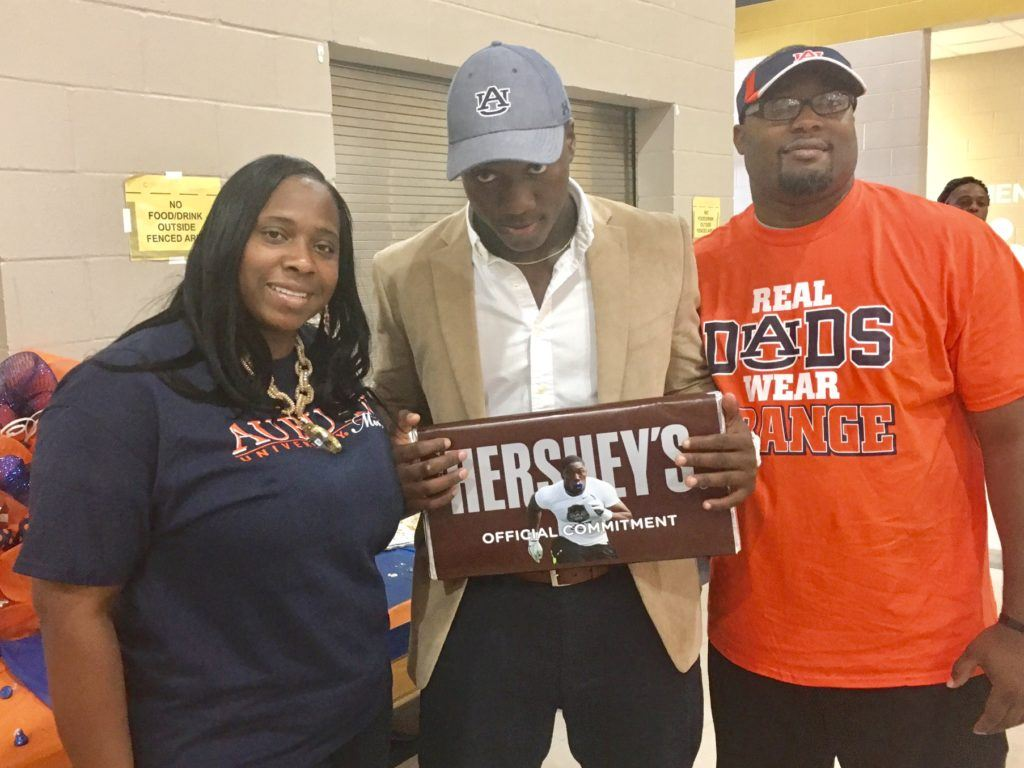 Oxford linebacker K.J. Britt stands with his parents holding the big chocolate bar he used to make his commitment to Auburn Monday.