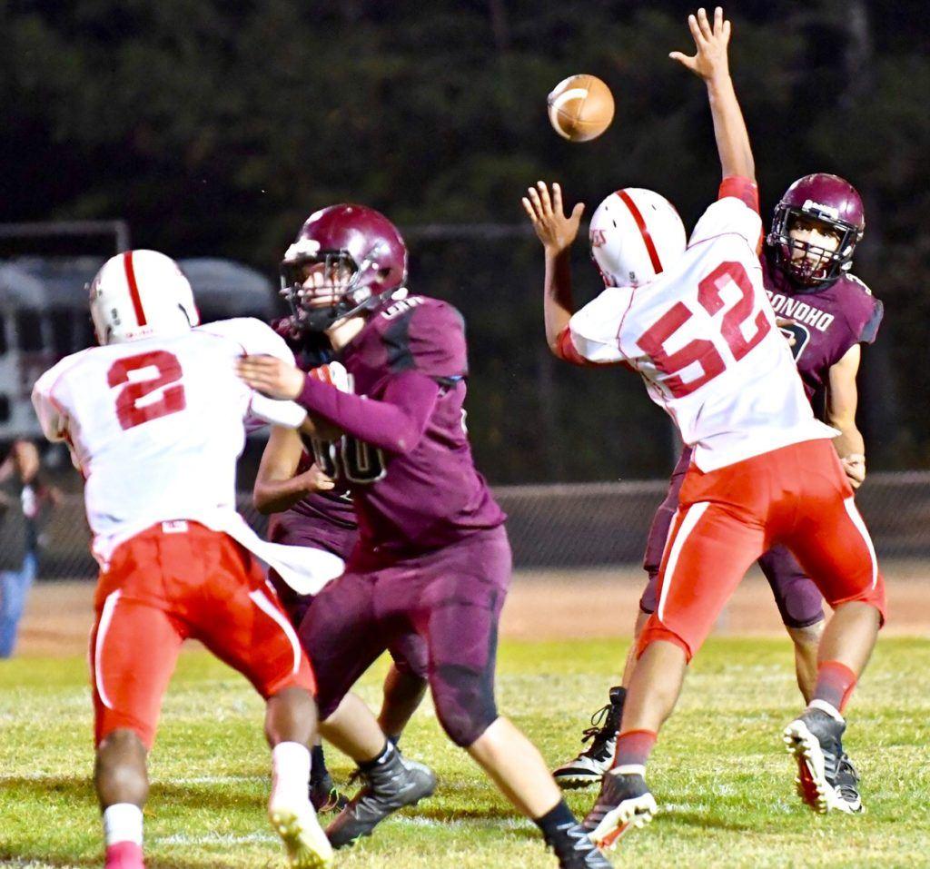 Donoho quarterback Garrett Steed tries to throw a pass around the pressure of Wadley lineman Chris Hodges.