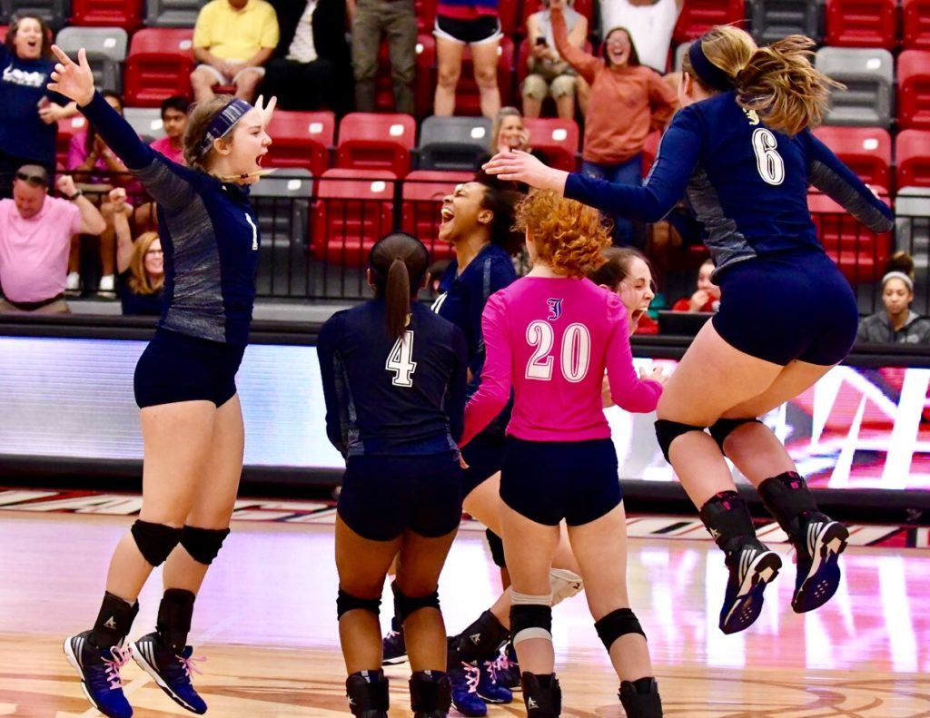 Jacksonville's players celebrate after the winning point drops in Monday's Calhoun County Volleyball Tournament final.