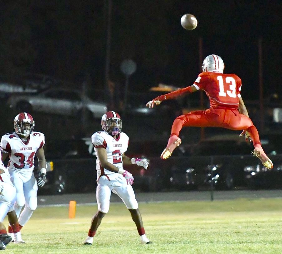 Saks' Brent Clark (13) gets way up in the air to defend the pass of Anniston quarterback Marrio Dobbins. The cover photo is action from the Anniston-Saks game. (Photos by B.J. Franklin/GungHo Photos)