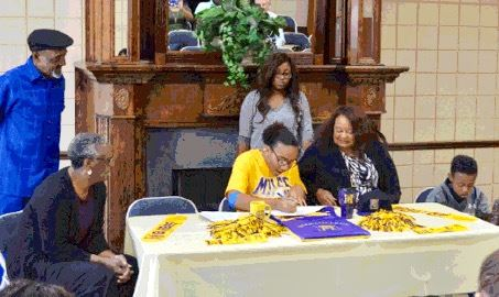 Jacksonville volleyball player Aniyah Robinson excitedly signs her scholarship papers to play for Miles College as her mother, sister look on.