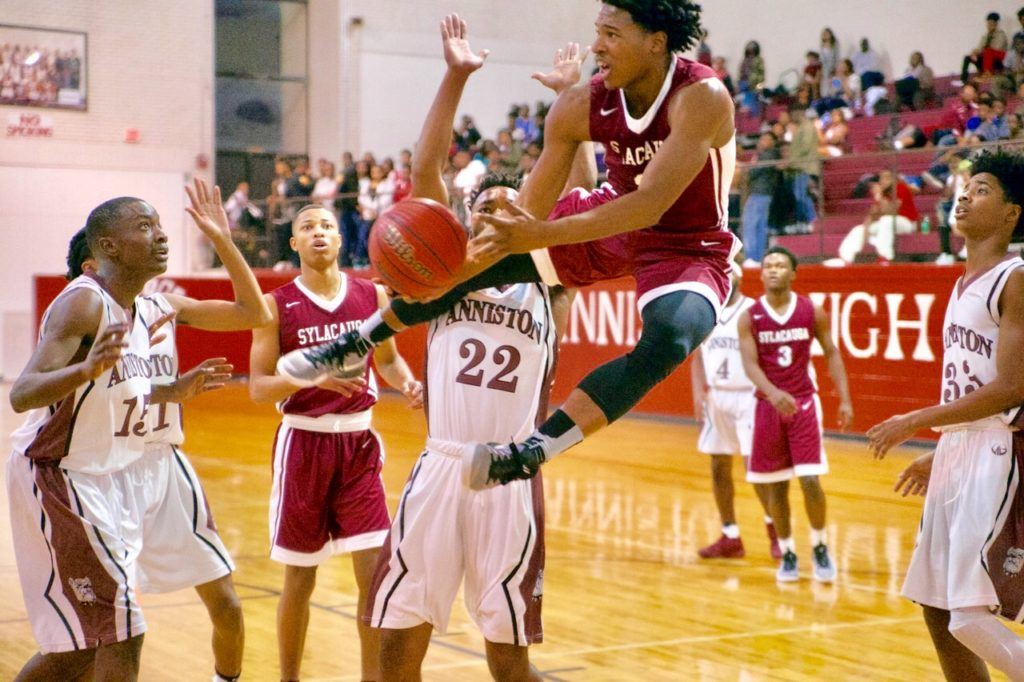All eyes are on Sylacauga's Malik Canford as he makes an acrobatic move in front of Anniston's Jakoey Bradford (15) and Tareeq Packer-Wood. (Photo by B.J. Franklin/GungHo Photos)
