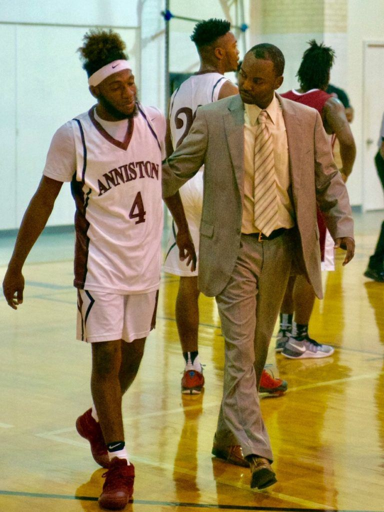 New Anniston basketball coach Torry Brown helps Marrio Dobbins back to the bench after the senior guard took an hard spill driving to the basket right before halftime. Dobbins scored 13 of his team-high 18 points in the second half. (Photo by B.J. Franklin/GungHo Photos)