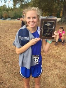 White Plains senior co-captain Alyssa Hudgins displays the Lady Wildcats' first-ever cross-country sectional championship plaque.