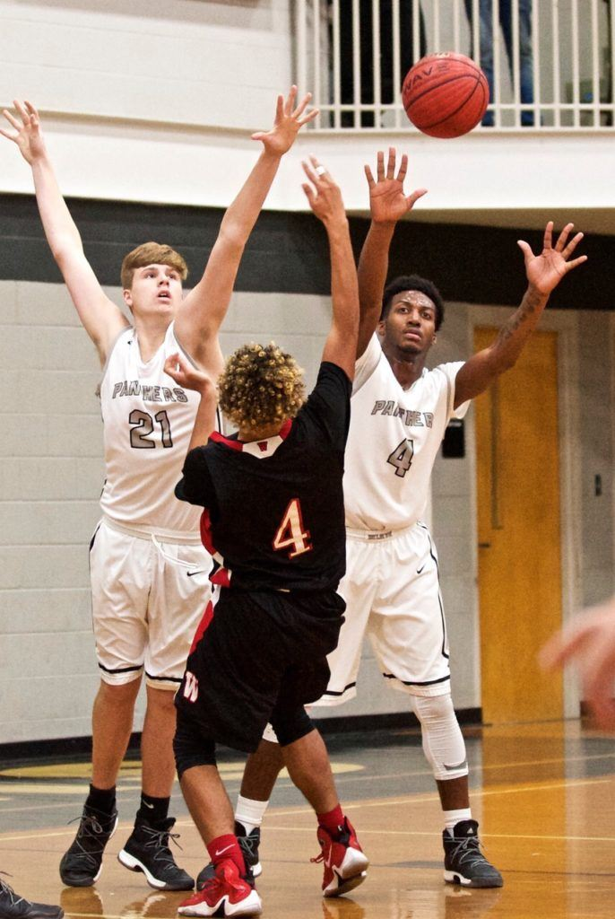Wellborn's Austin Cooper (21) and Jordan Montgomery (right) don't give Weaver's Robert Gaines much room to work. (Photo by B.J. Franklin/GungHo Photos)